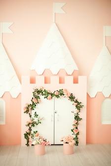 Pokój gier z różowym zamkiem dla dzieci. pokój dziecięcy dla małej księżniczki. dekoracje na przyjęcie dla dzieci. mały apartament księżniczki z różowym zamkiem i białymi drzwiami z kręconymi kwiatami.