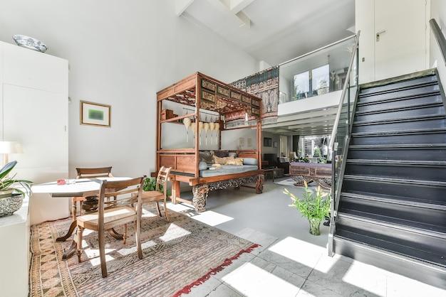 Pokój oświetlony słońcem z otwartym drugim piętrem i czarnymi schodami oraz ozdobnymi drewnianymi meblami w domu