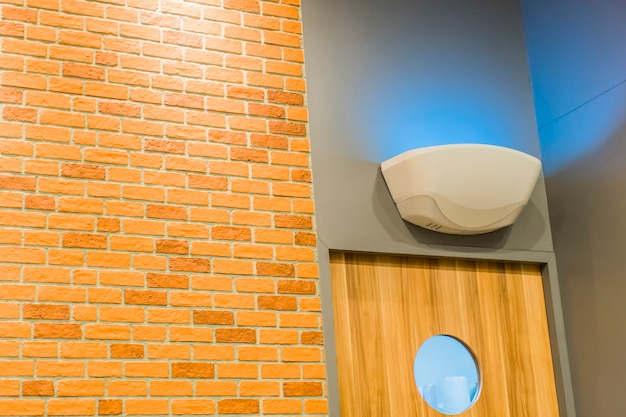 Pokój ozdobiony ceglanymi ścianami, drewnianymi drzwiami i niebieskimi lampami na paliwo.