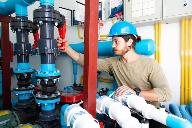 Pokój systemu czyszczenia basenu. profesjonalna obsługa i konserwacja pompy wody basenowej. technik pracujący.