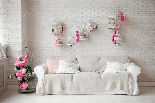 Pokój urządzony na walentynki z białą sofą i ozdobnymi klatkami
