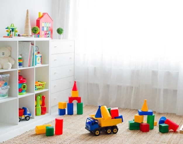 Pokój zabaw dla dzieci z plastikowymi kolorowymi klockami edukacyjnymi. podłoga do gier dla przedszkolaków. wnętrze pokoju dziecięcego. wolna przestrzeń. makieta tła
