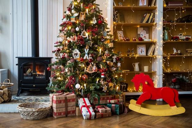 Pokój ze świątecznym wnętrzem, choinką ozdobioną świecącą girlandą i czerwonym fotelem na biegunach
