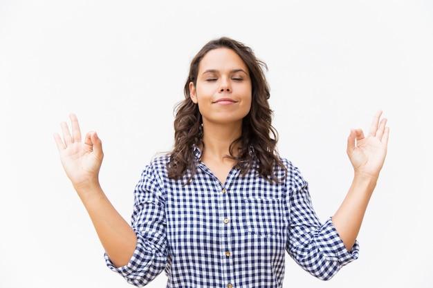 Pokojowa kobieta z zamkniętymi oczami robi ręki zen gestowi