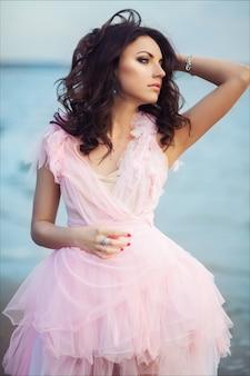 Pokojowa urlopowa raj kobieta chodząca na zmierzchu oceanu plaży. piękna dziewczyna w różowej romantycznej sukience