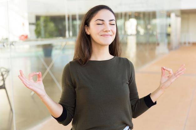 Pokojowa uśmiechnięta piękna kobieta robi zen gestowi