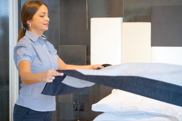 Pokojówka co łóżko w pokoju hotelowym. housekeeper making bed