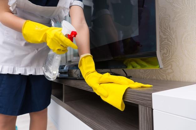 Pokojówka czyszcząca szafkę telewizyjną spryskując ją detergentem przed wytarciem ściereczką, z bliska na dłoniach w rękawiczkach