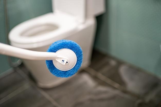 Pokojówka czyszczenie muszli klozetowej ze szczotką w łazience w domu.