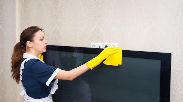 Pokojówka lub gospodyni sprzątająca telewizor odkurzanie blatu żółtą ściereczką ubrana w schludny mundur, profilowy widok górnej części ciała