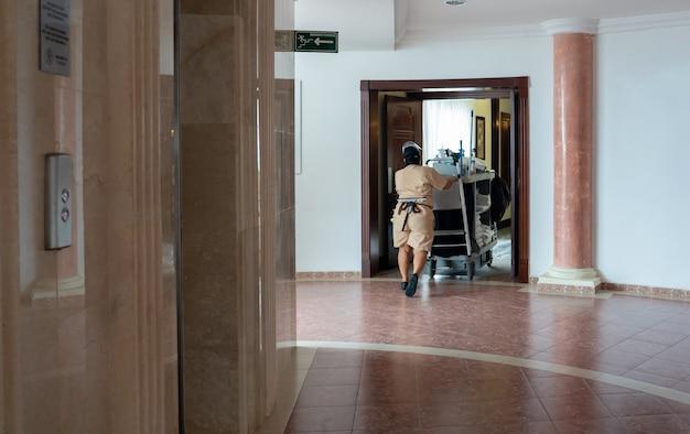 Pokojówka pchająca wózek wzdłuż korytarza w hotelowej pokojówce w pracy i wózku z zapasami do pokoju i?