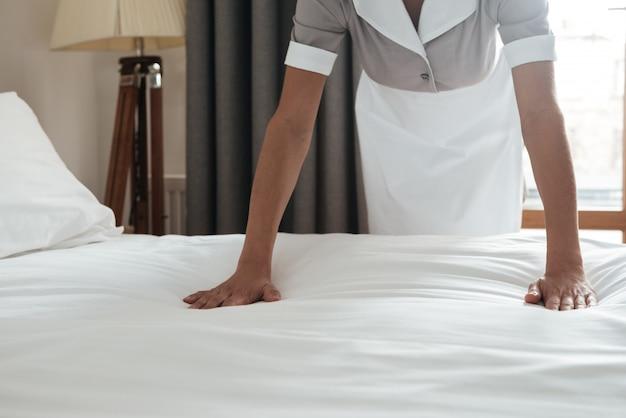 Pokojówka robi łóżko w pokoju hotelowym