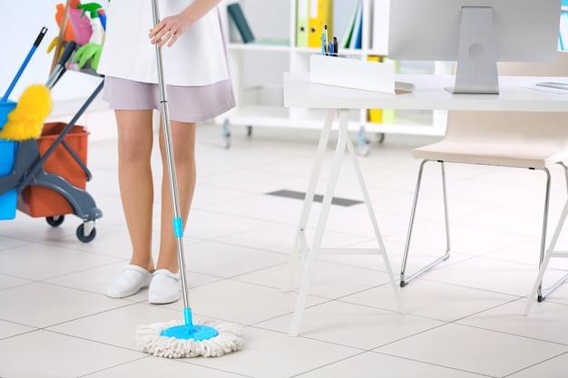 Pokojówka sprzątanie podłogi w biurze