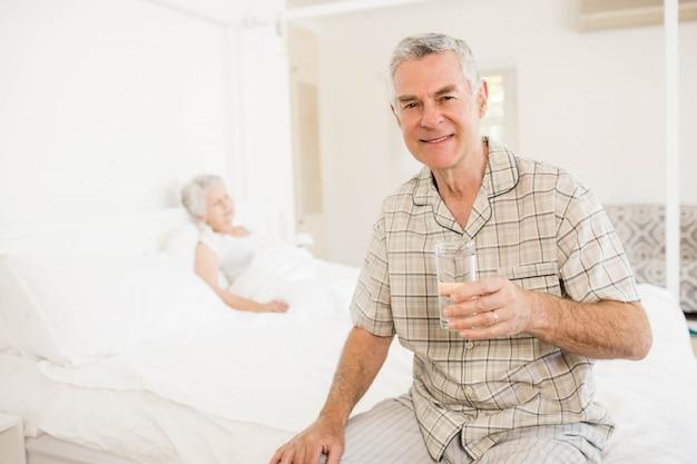 Pokojowy starszy mężczyzna trzyma szklankę wody w domu
