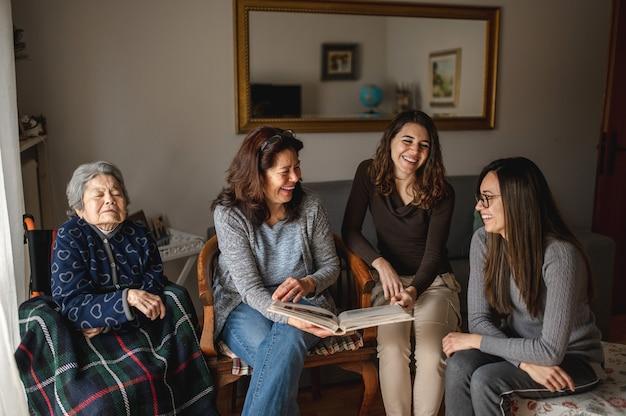 Pokolenie kobiet ze starą chorą babcią siedzącą na wózku inwalidzkim obok córki i wnuczek, patrząc na album ze zdjęciami