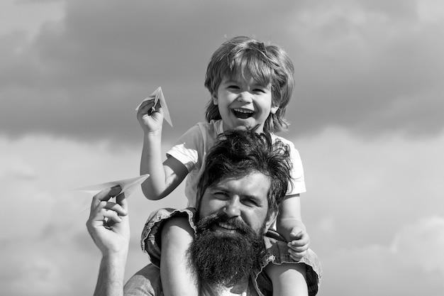 Pokolenie. ojciec daje synowi przejażdżkę z powrotem w parku. ojciec i syn razem budują papier