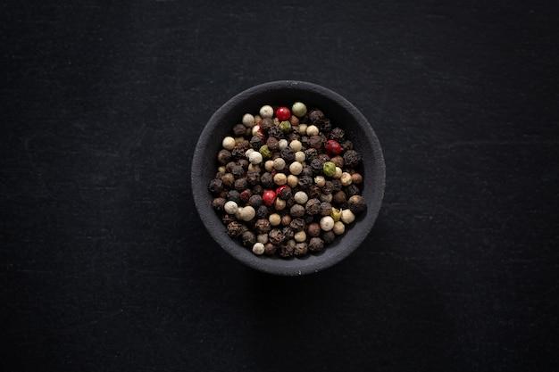 Pokoloruj całe ziarna pieprzu w małej misce na ciemnym tle.