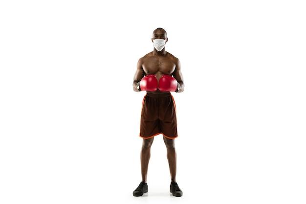 Pokonaj chorobę. męski bokser afro-amerykański w masce ochronnej. nadal aktywny podczas kwarantanny. opieka zdrowotna, medycyna, koncepcja sportu.