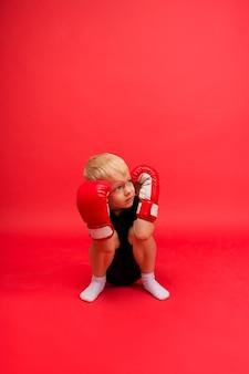 Pokonany bokser mały chłopiec siedzi w czerwonych rękawicach bokserskich na czerwono