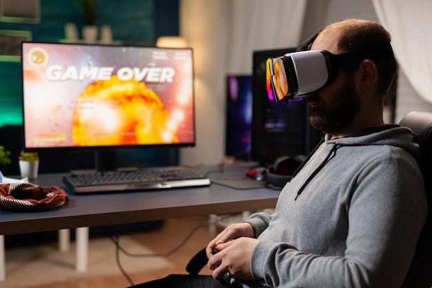 Pokonany gracz, przegrywający turniej gier wideo, grający z zestawem słuchawkowym rzeczywistości wirtualnej. konkurencyjny gracz używający joysticka do rywalizacji online późno w nocy w pokoju gier