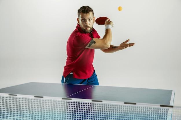 Pokonywanie. młody człowiek gra w tenisa stołowego na białej ścianie. modelka gra w ping ponga. pojęcie wypoczynku, sportu, ludzkich emocji w rozgrywce, zdrowego stylu życia, ruchu, akcji, ruchu.