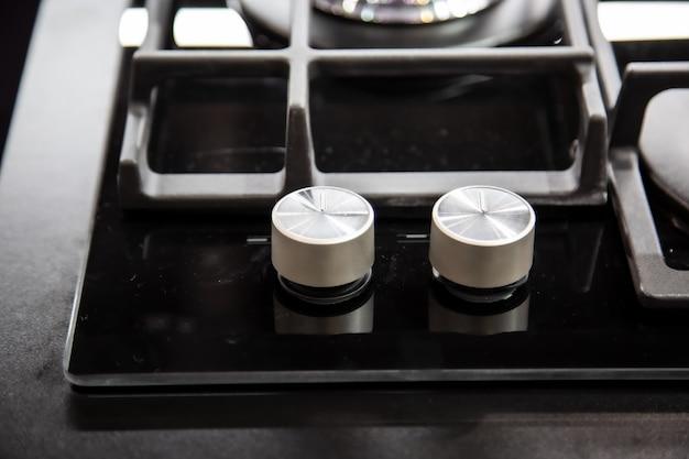 Pokrętła palnika gazowego z czarną lustrzaną powierzchnią kuchenki i grillami ze stali nierdzewnej, widok z góry blisko