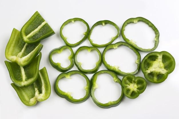 Pokroić na kawałki zieloną paprykę na białym tle