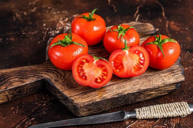 Pokrój czerwone pomidory koktajlowe na drewnianej desce do krojenia