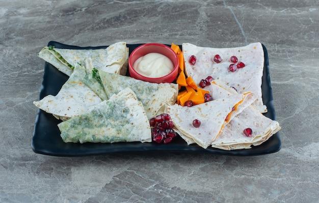 Pokrój dynię, lawasz, gutab i miskę majonezu na desce, na marmurowym stole.