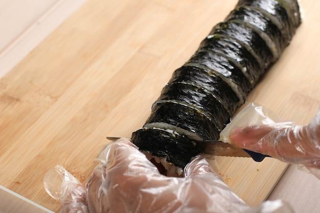 Pokrój kimbap (koreańskie danie z ryżu rolowanego) za pomocą niebieskiego noża. ręka kobiety nosząca plastikową rękawiczkę, wykonująca gimbap, cięty kimbap, koreański gimbap rolkowy (kimbob lub kimbap). robienie kimbopa krok po kroku