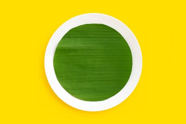 Pokrój liście bananowca w kształt koła na talerzu na żółtym tle.