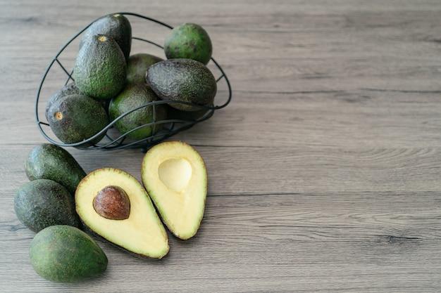 Pokrój na pół, pokrojone świeże zielone awokado na brązowym drewnianym stole. owoce koncepcja zdrowej żywności.