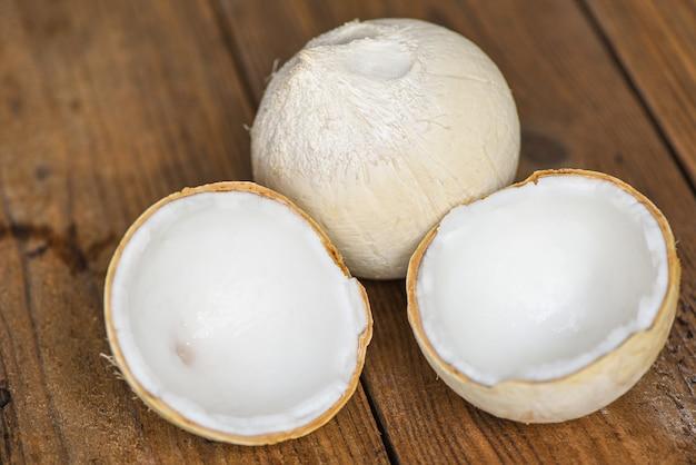 Pokrój pół kokosa i świeże orzechy kokosowe do jedzenia na drewnianym stole