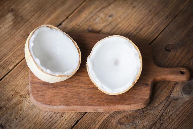 Pokrój pół kokosa i świeże orzechy kokosowe na starym drewnianym stole do jedzenia