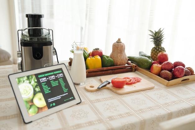 Pokrój pomidora, jogurt bez nabiału, świeże warzywa i cyfrowy tablet z przepisem na kuchennym stole