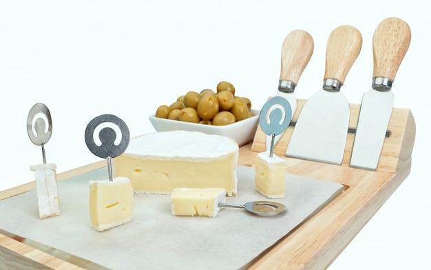 Pokrój ser w kostkę na drewnianej desce z oliwkami. zbliżenie.