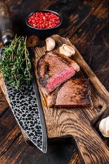 Pokrój smażony rumsztyk lub brazylijski stek wołowy picanha na drewnianej desce. ciemne drewniane tło. widok z góry.