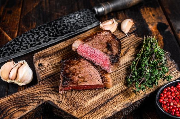 Pokrój smażony rumsztyk lub stek z brazylijskiej wołowiny picanha na drewnianej desce na drewnianym stole. widok z góry.