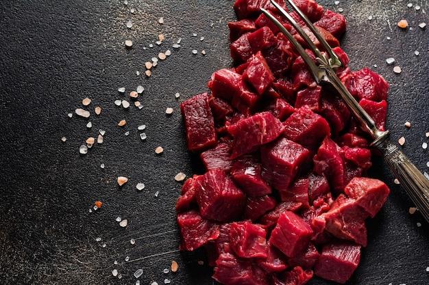 Pokrój wołowinę na małe kawałki solą morską, suszonymi ziołami i papryczkami chili na ciemnym łupku lub betonowej powierzchni