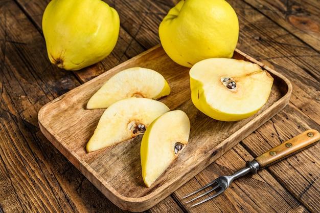 Pokrój żółte owoce pigwy na drewnianej tacy