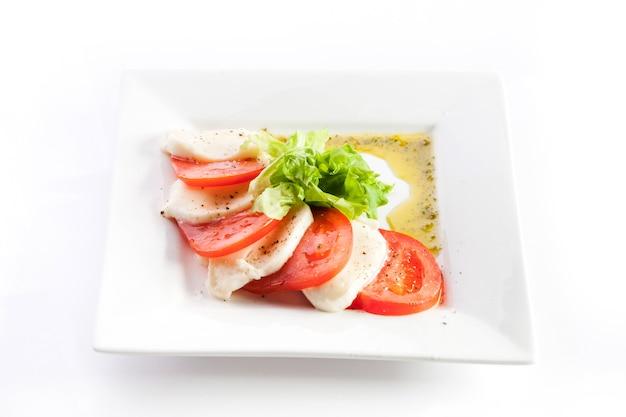 Pokrojeni pomidory i ser z sałatą na białym tle