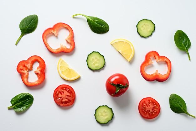 Pokrojeni warzywa i szpinak na białym tle