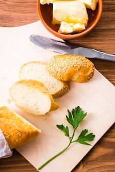 Pokrojona bagietka, masło i natka pietruszki na desce do krojenia.