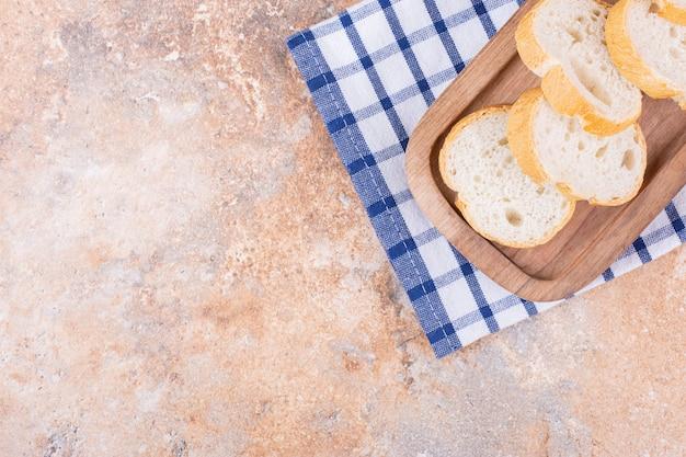 Pokrojona bagietka na drewnianym talerzu na ręczniku, na marmurze.