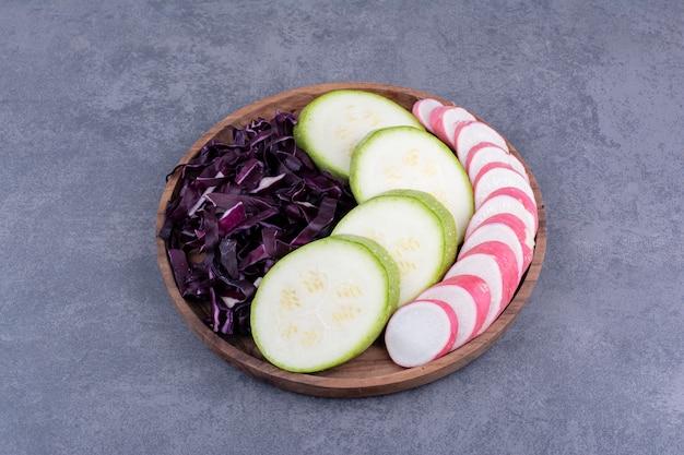 Pokrojona cukinia, kapusta fioletowa i rzodkiewka różowa na drewnianym talerzu.