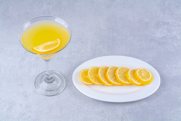 Pokrojona cytryna na talerzu obok szklanki soku pomarańczowego, na marmurowym stole.