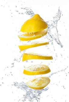 Pokrojona cytryna z wodą na białym odosobnionym tle