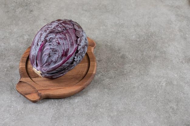 Pokrojona czerwona kapusta na drewnianym talerzu, na marmurowym stole.