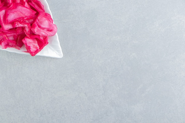 Pokrojona fioletowa kapusta na talerzu na marmurowej powierzchni
