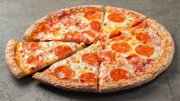 Pokrojona gorąca pizza pepperoni na brązowym tle.